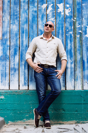 portrait full height of bald handsome man at shirt and jeans, boods. model making pose at blue wood baghround. summer mood at spring time Stock Photo