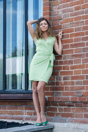 portret of girl in green dress ans shoes on red brick