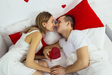 Valentines day bed lovely caucasian couple celebration red lay down gift from her to him