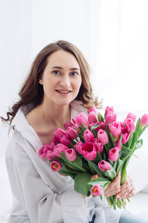 Portrait of young woman with pink tulips. White shirt