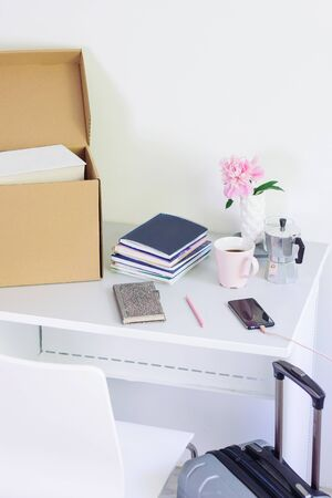 table with stationery, unpacking box with books. girl Back to college. Coffee, flowers, notebook Stock Photo