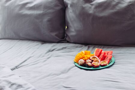 Plate with tropical fruit in grey bed, pilow background
