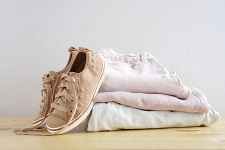 Children s snickers and stack of clothes. Jeans, shirt, kid snickers on wooden table and white background isolation.