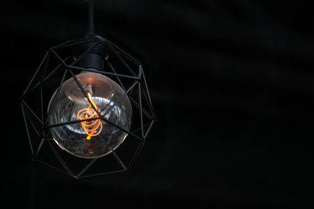Lamp with polygon metal frame on black background.
