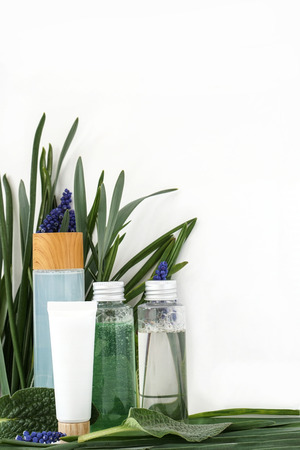 Reusable bottle with liquid. Skin care cosmetics on leaves flower and white background 版權商用圖片