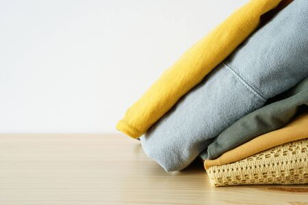 Stack of clothes on wooden table and white background Zdjęcie Seryjne