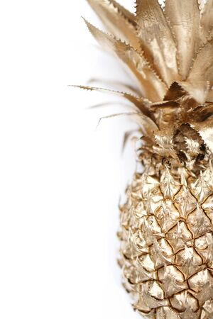 Gold painted pineapple on white background with space for text