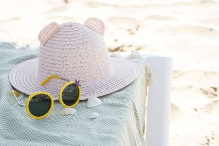 Kid s hat and sunglasses on the sun lounger in the beach Reklamní fotografie