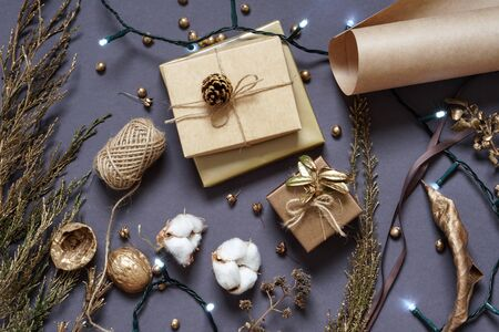 Gift boxes, natural packaging materials, craft paper, twine, ribbon , coniferous branch, led garland . Christmas and New year decor Photo