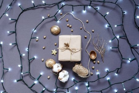 Gift wrapped in craft paper , decoration natural materials and led garland. Photo Stock Photo