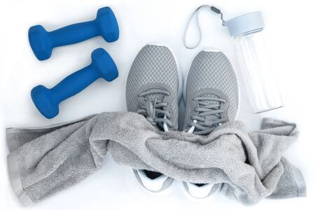 Sport equipment . Running shoes, blue dumbbells, water bottle towel . Flat lay composition