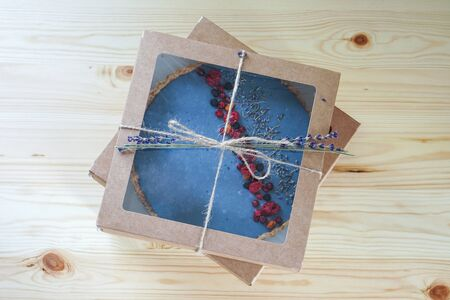 Homemade cake with freeze-dried berries packed in an eco box. Lavender flowers decor. Photo