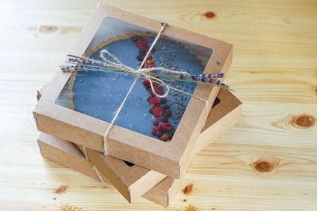 Homemade cake with freeze-dried berries packed in an eco box. Lavender decor. Photo Imagens