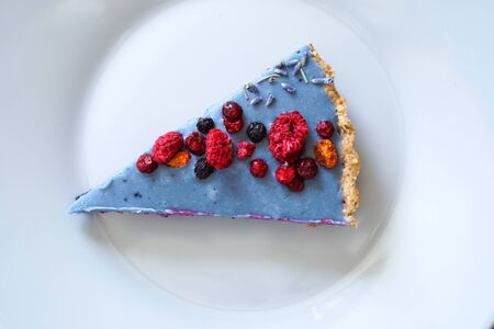 Slice of homemade cake decorated with freeze- dried berries. Photo