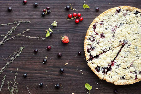 Homemade pie with berries on wooden table texture. Summer photo receipts