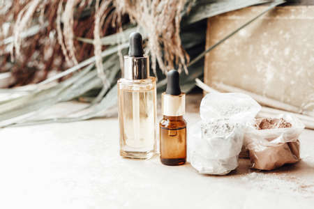 Glass bottles with natural oil and bags of cosmetic clay for face and body care. Palm leaves on background.