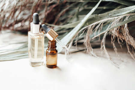 Glass bottles with natural oil for face and body care. Palm leaves on background