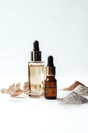 Glass bottles with oil and handfuls of different colors cosmetic clay for face and body care. Photo content