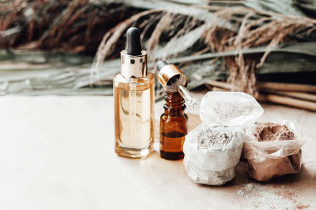 Glass bottles oil and bags of different colors cosmetic clay for face and body care. Palm leaves on background. Natural cosmetics. Photo