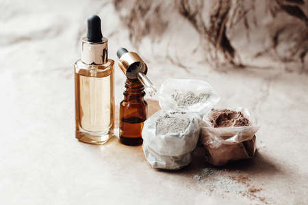 Glass bottles with oil and bags of different colors cosmetic clay for face and body care. Photo
