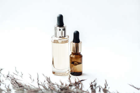 Glass bottles with oil for face and body care on white background. Natural cosmetics. Photo content