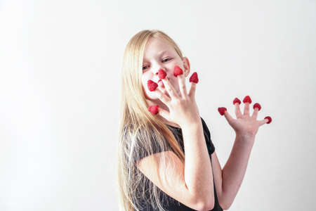 Girl with a big raspberry on her fingers. Photo