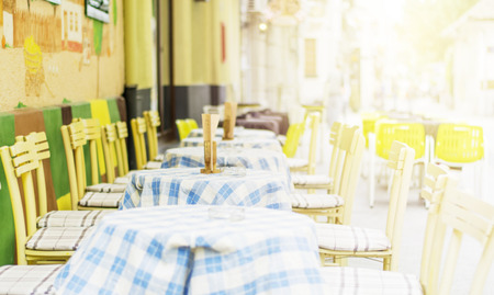 business backgound: Background of blurred cafe on street of city. Tables and chairs outside in natural bokeh Stock Photo