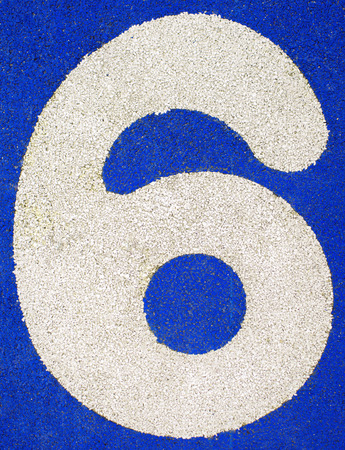number six: Number six on a running track. White number on blue background. Stock Photo