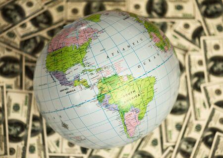 Globe lying on the background full of money, showing America.
