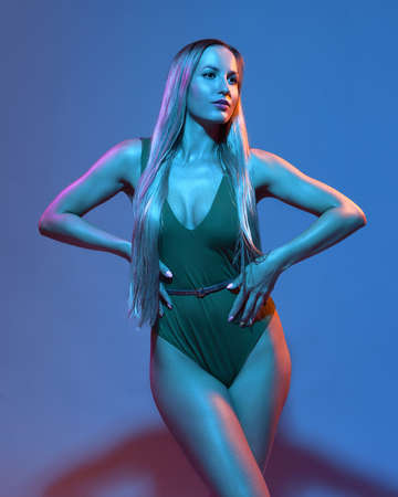 Beautiful attractive glamorous female in green swimsuit with blond long hair illuminated with colourful gel lights - blue, orange, pink Imagens