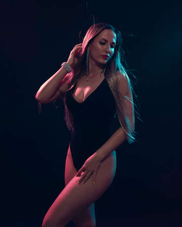 Beautiful attractive glamorous female in black body with blond long hair illuminated with colourful gel lights - turquoise and pink and wearing diamond earrings and bracelet