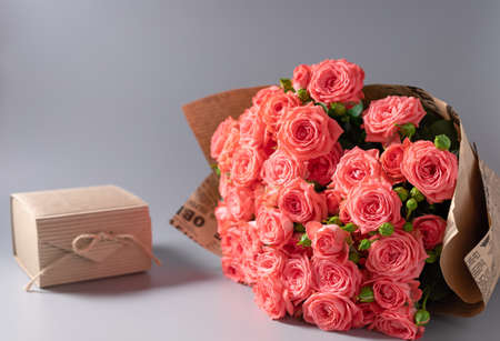 bouquet of pink roses in craft paper and a gift box