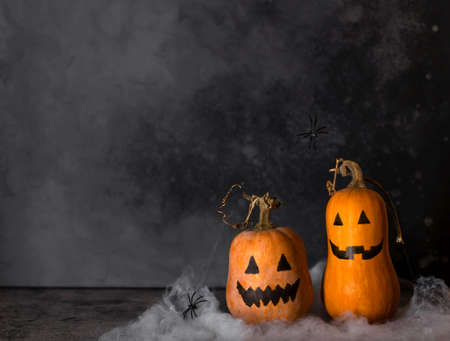 Halloween pumpkins with painted faces and spider web with hanging spiders