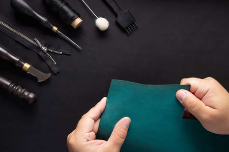 Leather Craftsman holding green leather sample and tool kit for handcraft wallets.