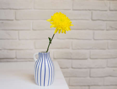Fresh yellow flower in a vase on a background of a white brick wall. Scandinavian interior.