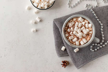 mug with a hot drink and mini marshmallows in a festive atmosphere. white background with copy space