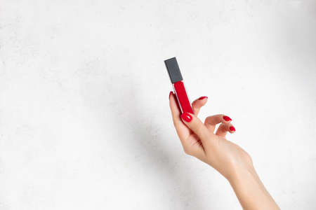 womans hand with red manicure holding red liquid matte lipstick on white background.
