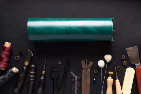 roll of green leather and various tools for handcrafting leather products. 版權商用圖片