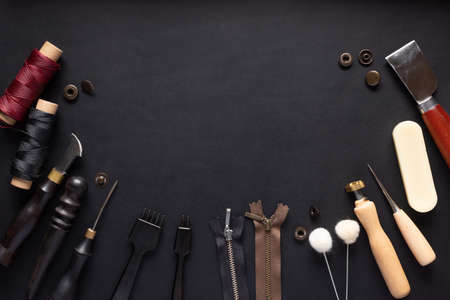 set of different tools for making leather goods on black leather background.