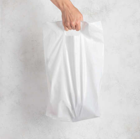 white plastic bag held by a womans hand. light background.