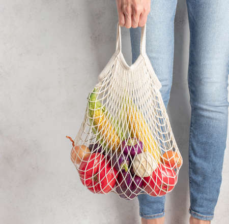 young woman holding a reusable mesh bag with fresh vegetables. grey background, zero waste concept Фото со стока