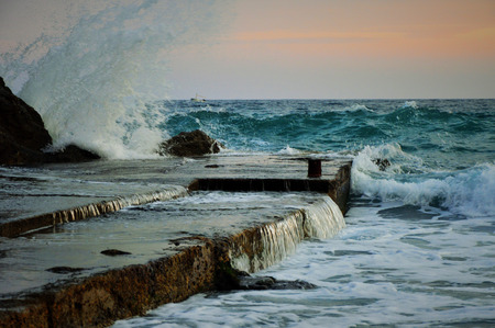 Strong waves crashing into a rocky docks  on a dreamy sunset Stock Photo