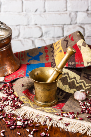 oriental rug: Bronze kitchen utensils for grinding spices