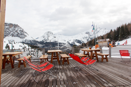 lounge chairs: Terrace at a ski resort with red lounge chairs. Stock Photo