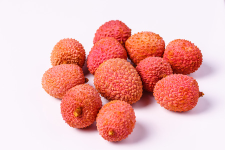referred: Several litchi lying on a white table. Still referred to as the Chinese lychee, plum or Chinese Stock Photo