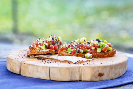 Salmon tartare with avocado on toasted bread is on the saw cut of a log.