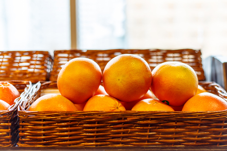 shelf: Oranges in a wicker basket on the supermarket shelf.