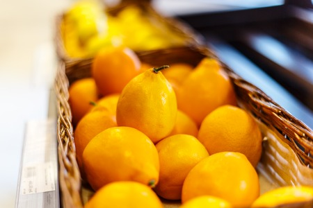 shelf: Lemons in a wicker basket on the supermarket shelf. Stock Photo