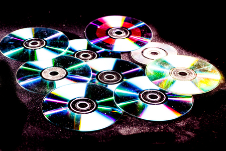 cd rom: Multiple disks, this can be a DVD or CD lying on a black background. On disks reflects the rainbow.