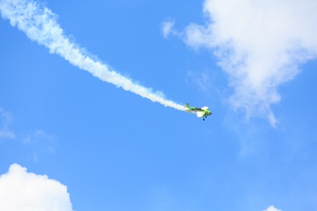 Little green plane performs aerobatics in the sky.